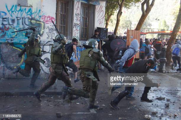 Demonstrators run away from riot police during a protest against President Sebastian Piñera on November 19 2019 in Santiago Chile Representatives...