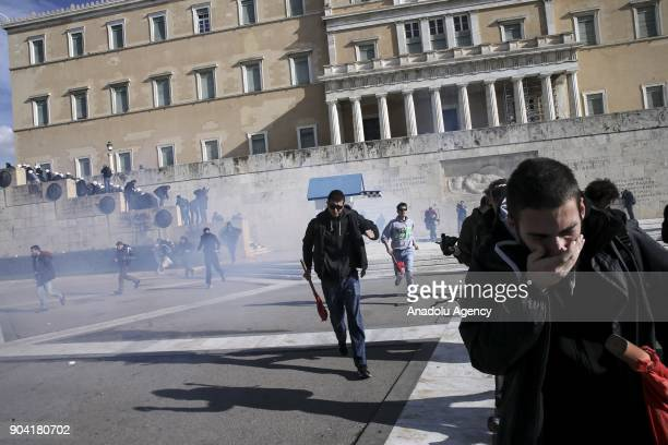 Demonstrators run away from the tear gas launched by riot police after they attempted to enter the parliament building during a protest against the...
