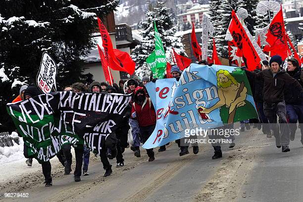 Demonstrators run during a rally against the annual meeting of the World Economic Forum attended by the world's business and political elite on...