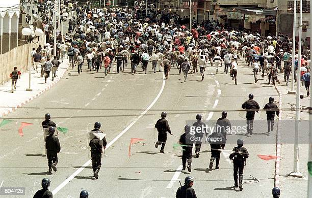 Demonstrators run from police during riots April 26 2001 in the Berber capital of Tizi Ouzou Algeria 62 miles east of Algiers Rioting started after a...