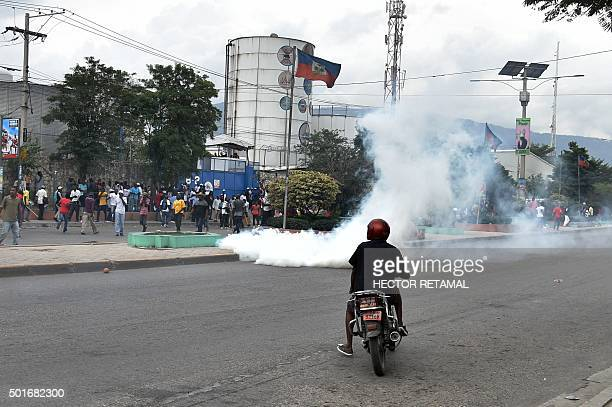 Demonstrators run from tear gas as they march to the Ballot Tabulation Center in Sonapi to protest against the Provisional Electoral Council the...