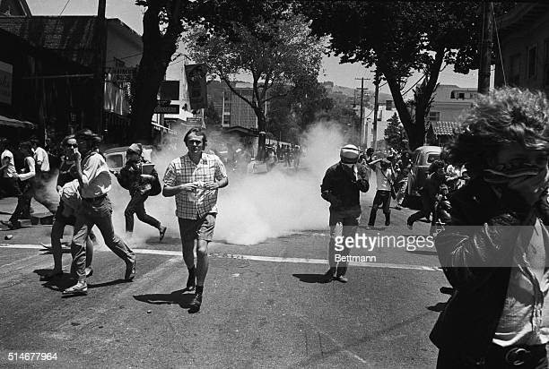 Demonstrators run from tear gas thrown at them by police after a new confrontation over People's Park.