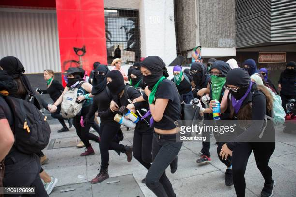 Demonstrators run from the police during a rally on International Women's Day in Mexico City Mexico on Friday March 8 2020 The United Nations first...