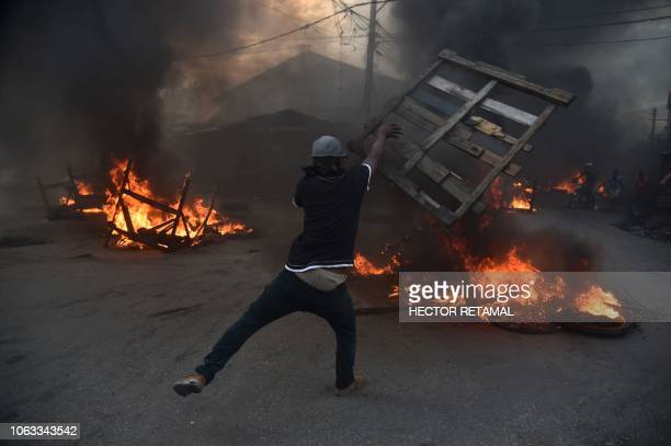 Demonstrators run next to burning barricades during a protest demanding accountability from politicians for allegedly squandering billions of dollars...