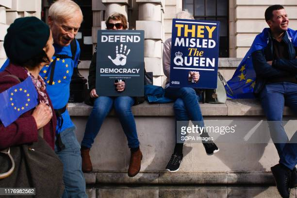 Demonstrators seat with placards on a wall on Whitehall during the protest A mass 'Together for the Final Say' march organised by the 'People's Vote'...