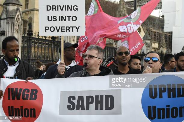 Demonstrators seen blowing whistles during the protest Minicab drivers blocked Parliament Square in protest over changes to the congestion charge...