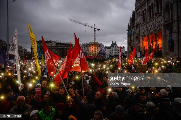 Demonstrators seen holding their smartphone lights during a protest in Heroes Square against the enactment of a recent labor law also called the...
