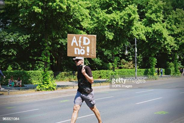 A demonstrators seen walking while holding a placard saying 'AFD no ' during the demonstration Techno lovers and anti racism activists have marched...