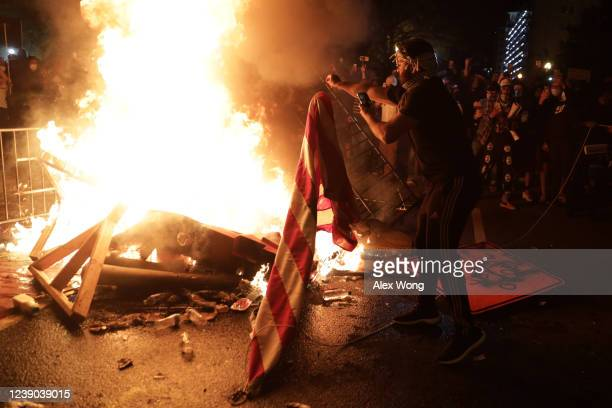 Demonstrators set a fire and burn a U.S. Flag during a protest near the White House on May 31, 2020 in Washington, DC. Minneapolis police officer...