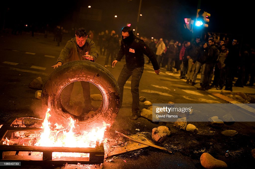 Demonstrators set up a barricade of burning tires at the main entrance of Mercabarna, the biggest wholesale market in the city, at the beginning of a 24-hour strike on November 14, 2012 in Barcelona, Spain. Spain's trade unions have called for today a general strike, the second of Mariano Rajoy's presidency. Protestors from social movements are expected to join striking public sector workers to demonstrate against austerity cuts, labour reforms and an unemployment rate of 25 percent.