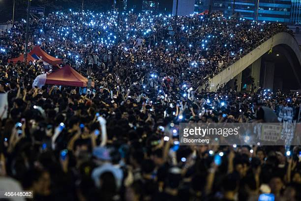Demonstrators shine lights from their mobile devices as they hold them aloft during a ongoing protest outside the central government office in Hong...