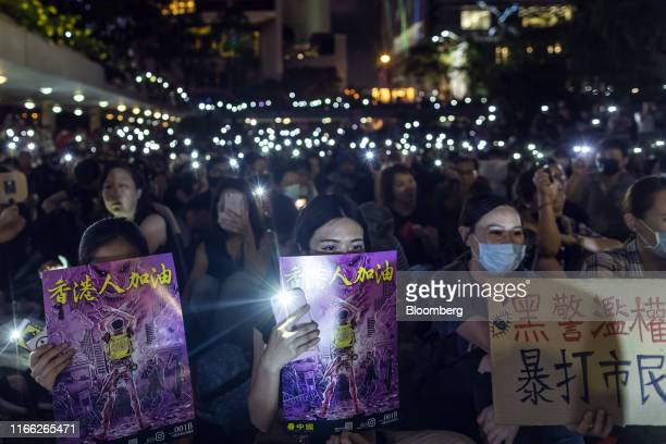 Demonstrators shine lights from their smartphones while holding placards during a rally organized by the Social and Political Organizations Workers...