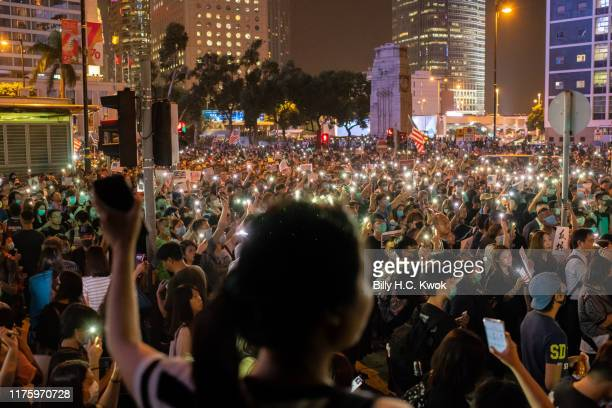 Demonstrators shine their cellphones and wave US national flags during a rally in support of the Hong Kong Human Rights and Democracy Act on October...