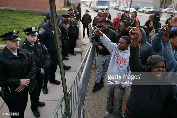 Demonstrators shout at Baltimore Police officers as they stand guard outside the Western District station during a protest against police brutality...
