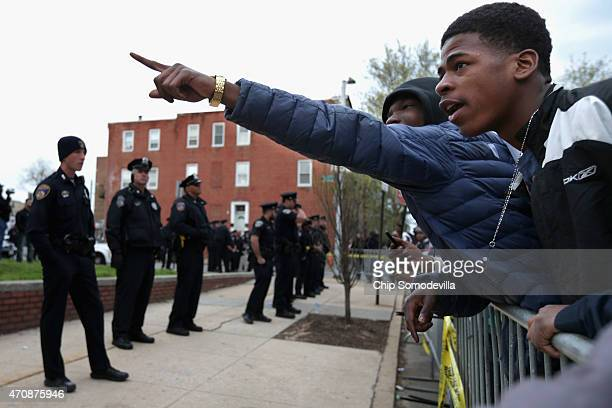 Demonstrators shout insults at officers in front of the Baltimore Police Western District station after marching from Baltimore City Hall to protest...