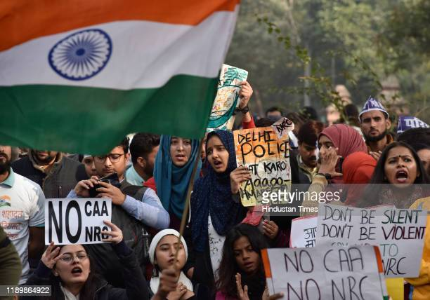 Demonstrators shout slogans and hold placards as they attend a protest against a Citizenship Amendment Act , at Jamia Millia University on December...