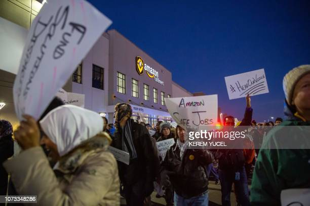 Demonstrators shout slogans and hold placards during a protest at the Amazon fulfillment center in Shakopee Minnesota on December 14 2018 A group of...