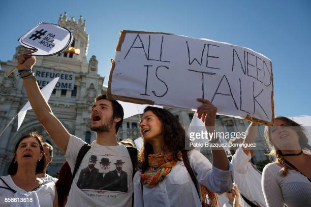 Demonstrators shout slogans and hold placards reading 'Do we talk' and 'All we need is talk' during a protest in front of Madrid City Hall under the...