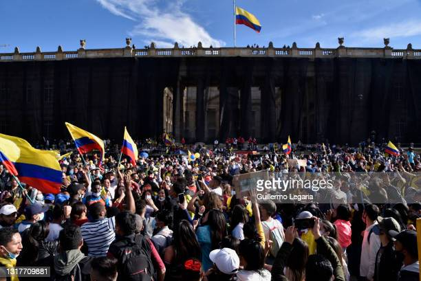 Demonstrators shout slogans and wave flags as they gather in front of the Congress building at Bolivar square during national strike against Ivan...