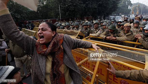 Demonstrators shout slogans as Policemen are trying to stop them from approaching a barricade on their way to India Gate while protesting against a...