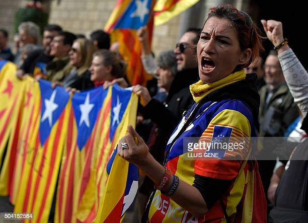 Demonstrators shout slogans as they hold proindependence Catalan flags during a demonstration in front of the Catalan regional government...