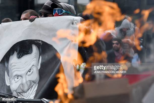 TOPSHOT Demonstrators shout slogans as they march with a banner depicting French President next to burning trash during a rally in Rennes on...