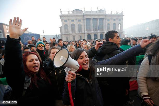 """Demonstrators shout slogans during a protest against austerity measures in """"Piazza Castello"""", in Turin on December 11, 2013. AFP PHOTO/MARCO..."""