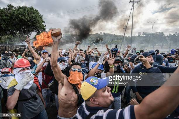 Demonstrators shout slogans while a barricades seen burning in the background during a demonstration against Nicolas Maduro policies Rally against...