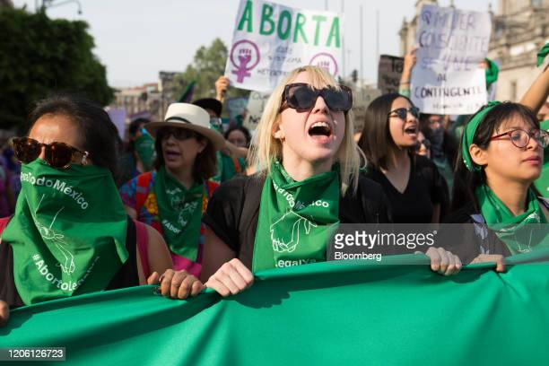 Demonstrators shout slogans while holding a banner during a rally on International Women's Day in Mexico City Mexico on Friday March 8 2020 The...