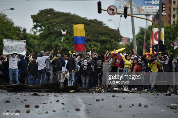 Demonstrators shout towards riot police officers during clashes following a protest against a tax reform bill launched by President Ivan Duque, in...