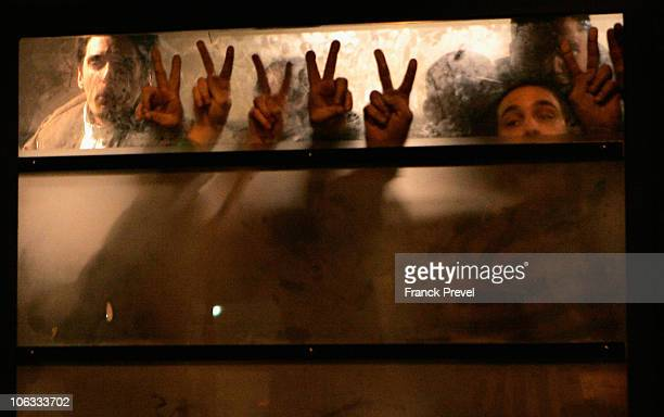 Demonstrators show the victory sign through the window of a police bus after being arrested at the end of a protest against the pension reforms on...
