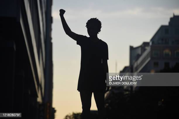 A demonstrator's silhouette is seen as they a fist during a protest against police brutality and the death of George Floyd near the White House on...