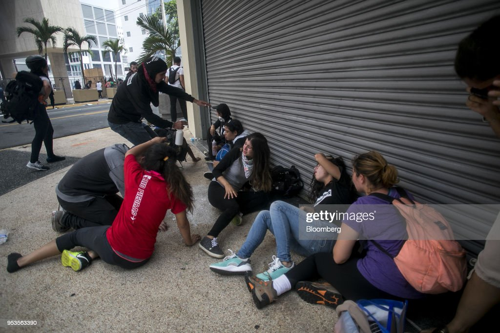 Demonstrators sit after being pepper-sprayed during a protest against austerity measures in the Hato Rey neighborhood of San Juan, Puerto Rico, on Tuesday, May 1, 2018. Puerto Rico demonstrators battled police on San Juan's streets as they marched against proposed cuts to retirement benefits and looser labor laws as the bankrupt island seeks to reduce $74 billion of debt. Photographer: Xavier Garcia/Bloomberg via Getty Images