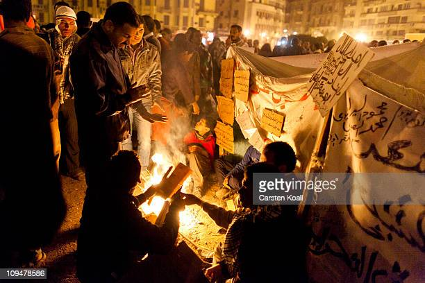Demonstrators sit around a camp fire in front of makeshift tents February 27 2011 in Cairo Egypt Many protesters have gathered in Tahrir Square after...
