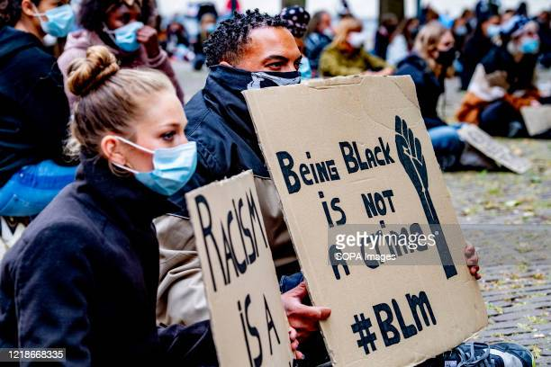 Demonstrators sit at the Abbey Square with their placards during an antiracism protest As a result of the death of George Floyd while he was detained...