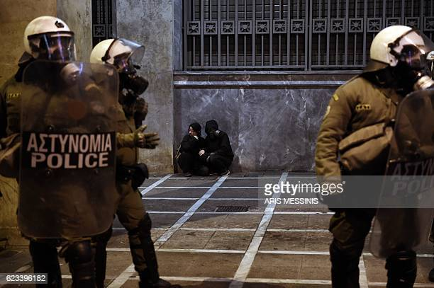 TOPSHOT Demonstrators sit behind Greek riot police during a protest against the visit of the US president in Athens on November 15 2016 US President...