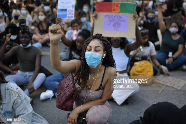 Demonstrators sit down in the road outside the US Embassy in London on May 31, 2020 to protest the death of George Floyd, an unarmed black man who...