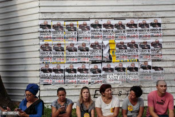 Demonstrators sit in front of a wall displaying signs against a prison sentence for Luiz Inacio Lula da Silva Brazil's former president during a...