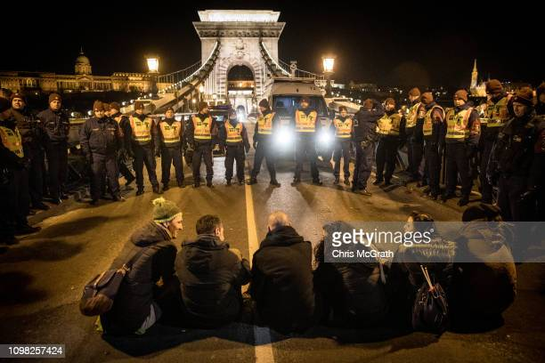 Demonstrators sit in front of police on Budapest's famous Szechenyi Chain Bridge after police blocked them from leaving after attending a...