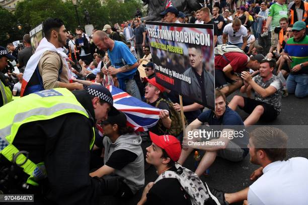 Demonstrators sit in the road after clashing with police during a 'Free Tommy Robinson' protest on Whitehall on June 9 2018 in London England...