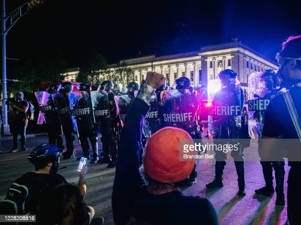 Demonstrators sit in the street in front of law enforcement on August 25 2020 in Kenosha Wisconsin As the city declared a state of emergency curfew a...