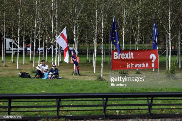 Demonstrators sit near England's national flag of St George a Union flag also known as a Union Jack and an European Union flag ahead of the...