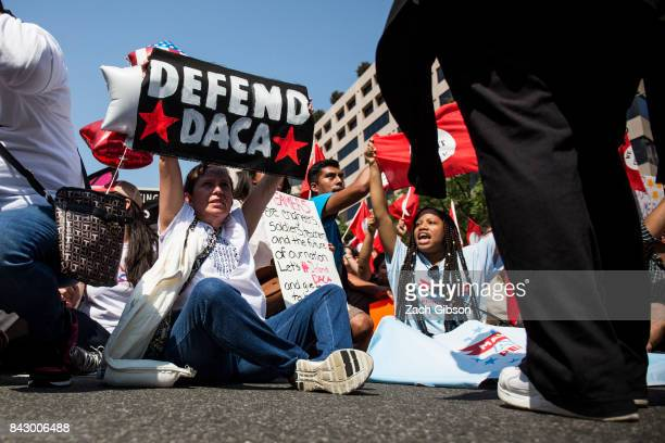 Demonstrators sit on Pennsylvania Avenue during a demonstration in response to the Trump Administration's announcement that it would end the Deferred...