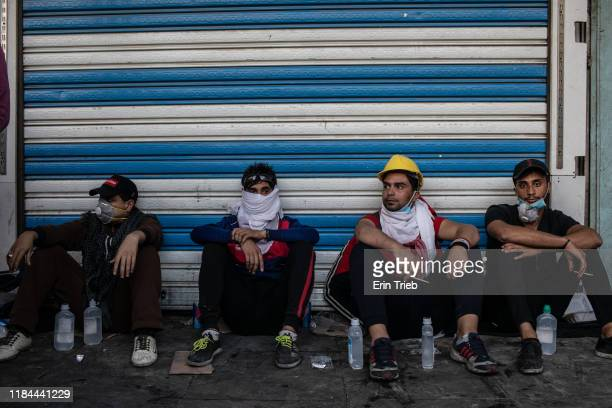 Demonstrators sit with eyewash solution they use to help those effected by teargas near Ahrar Bridge where there have been recent clashes between...