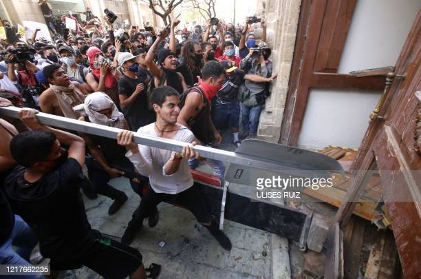 Demonstrators smash a door during a protest following the death of a young man while in police custody, after he had been arrested allegedly for...