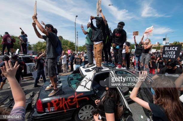 Demonstrators smash a police vehicle in the Fairfax District as they protest the death of George Floyd, in Los Angeles, California on May 30, 2020. -...