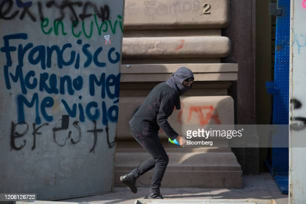A demonstrators sprays graffiti on a wall during a rally on International Women's Day in Mexico City Mexico on Friday March 8 2020 The United Nations...