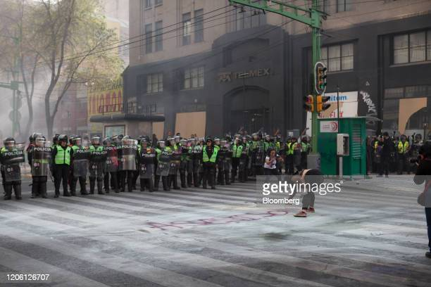 A demonstrators sprays paint the ground during a rally on International Women's Day in Mexico City Mexico on Friday March 8 2020 The United Nations...