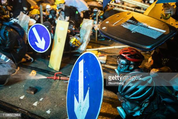 Demonstrators sprays water using a fire hose while standing off against riot police during a protest in the Sheung Wan district of Hong Kong, China,...