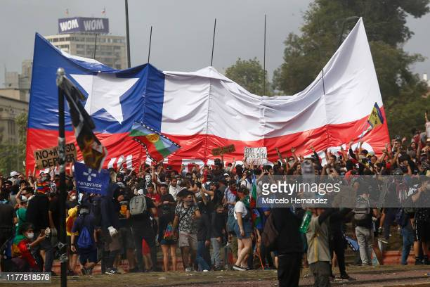 Demonstrators spread a giant flag of Chile as they gather at Plaza italia against President Sebastian Piñera during the sixth day of protest against...